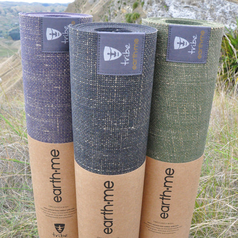 Three Earth.Me yoga mats (Amethyst, Cosmos & Olive colours) standing vertically side by side in a paddock - TRIBE | Eco Yoga Store