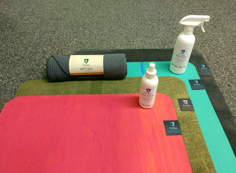 TRIBE Wanderer Travel Mats, Earth Me & Wanderer Yoga Mats on top of each other with TRIBE Eco Clean Mat Cleaner bottles & a TRIBE Get a Grip Yoga Towel | Eco Yoga Store