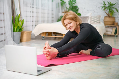Woman practicing yoga in her bedroom following an online yoga class | Eco Yoga Store