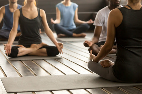 Yoga practice in the yoga studio - teacher and students in asana | Eco Yoga Store