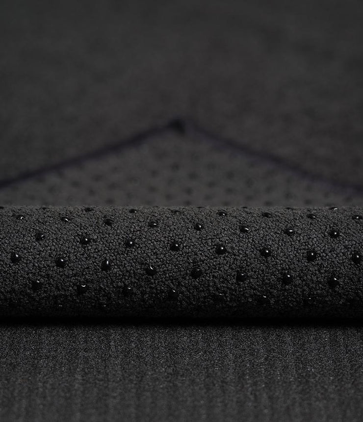 Manduka Yogitoes Mat Towel - Onyx - corner folded over showing underside | Eco Yoga Store