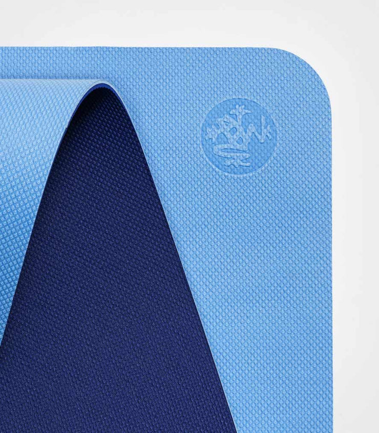 Manduka Begin Mat 5mm Yoga Mat - Light Blue - top corner loosely rolled showing both sides | Eco Yoga Store