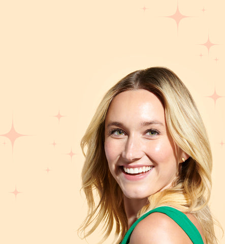 a woman surrounded by little stars smiling over her shoulder with glowy, healthy skin