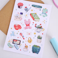Sticker sheet containing 16 different vinyl stickers, in pastel colors, featuring home items: a videogame console, some planters, writing materials, a book, plush toys, a key, a lock, and an origami figure.