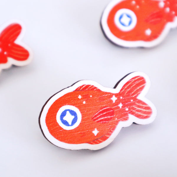 Wooden pin featuring an orange fish.