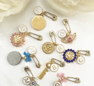 small pin with letter/charm