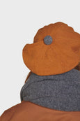 Knitted lambs wool beret in burnt orange designed and made in the UK. Sustainable British knitwear label.
