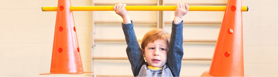 Child holding up a bar with two cones