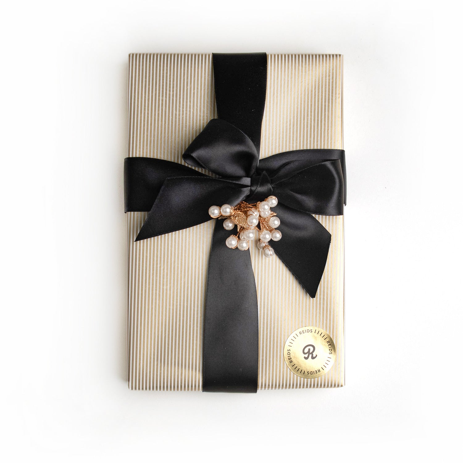 1 lb fancy wrapped box. Gold, and white pin-stripped wrapping paper. Tied with a black satin ribbon and white decorative piece