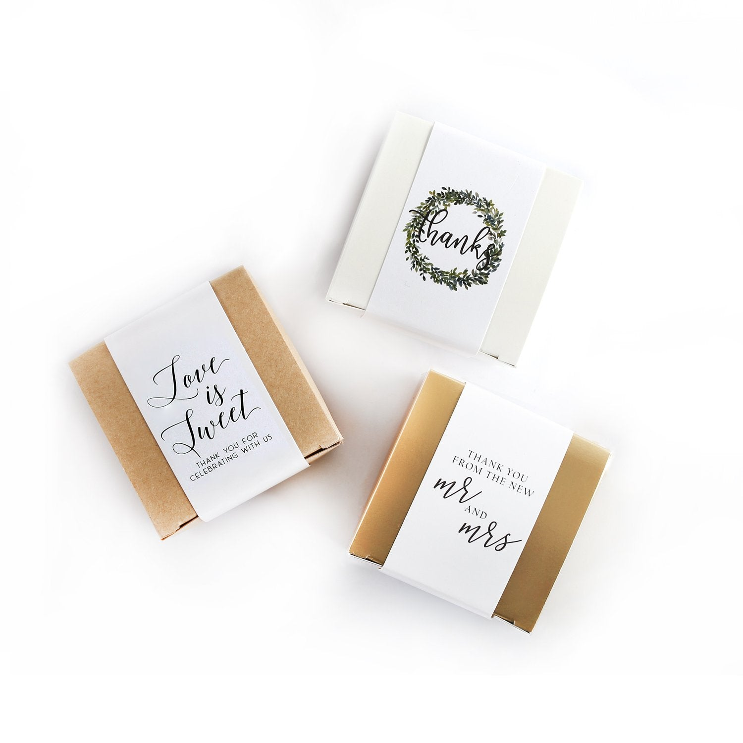 Product photo of paper band options. 'Love is sweet' in a cursive black font. 'Thanks' in a cursive black font with wreath image. 'Mr and Mrs' in black cursive font.