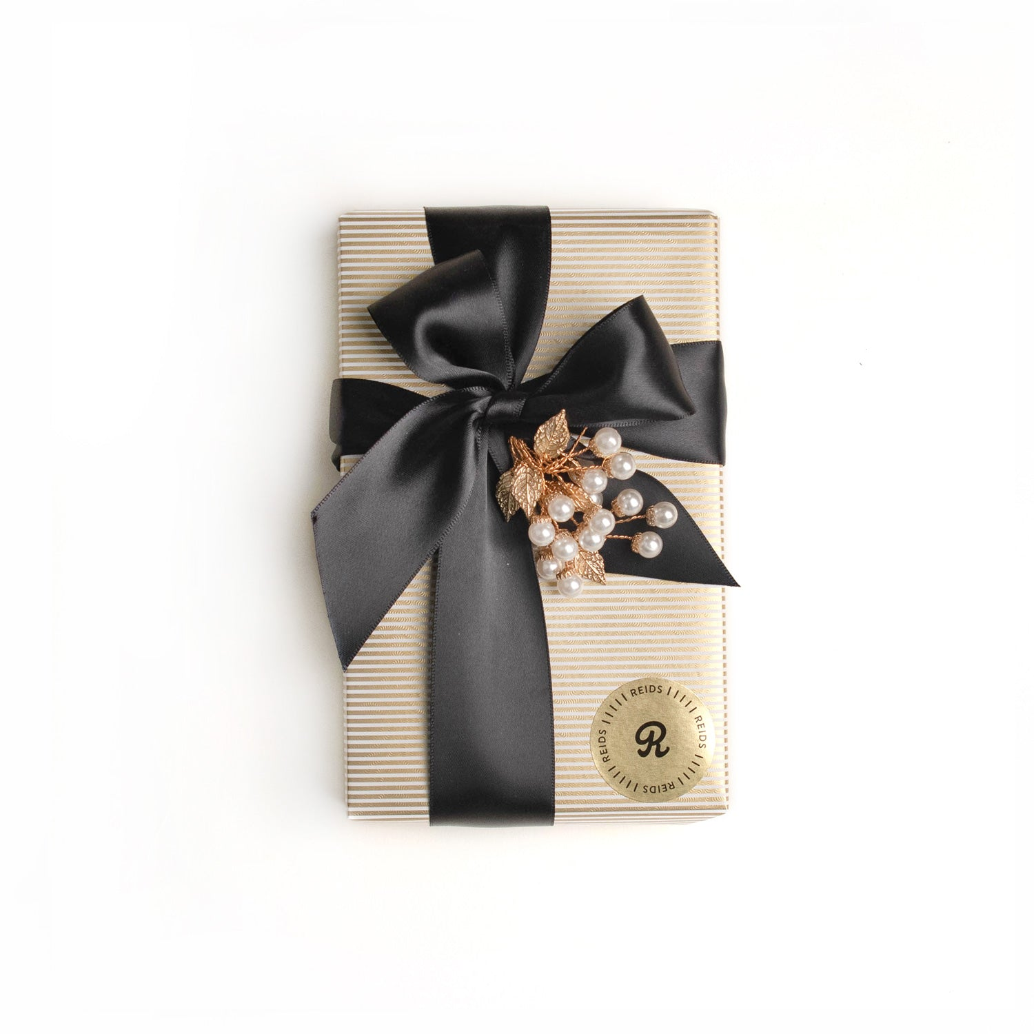 1/2 lb fancy wrapped box. Gold, and white pin-stripped wrapping paper. Tied with a black satin ribbon and white decorative piece