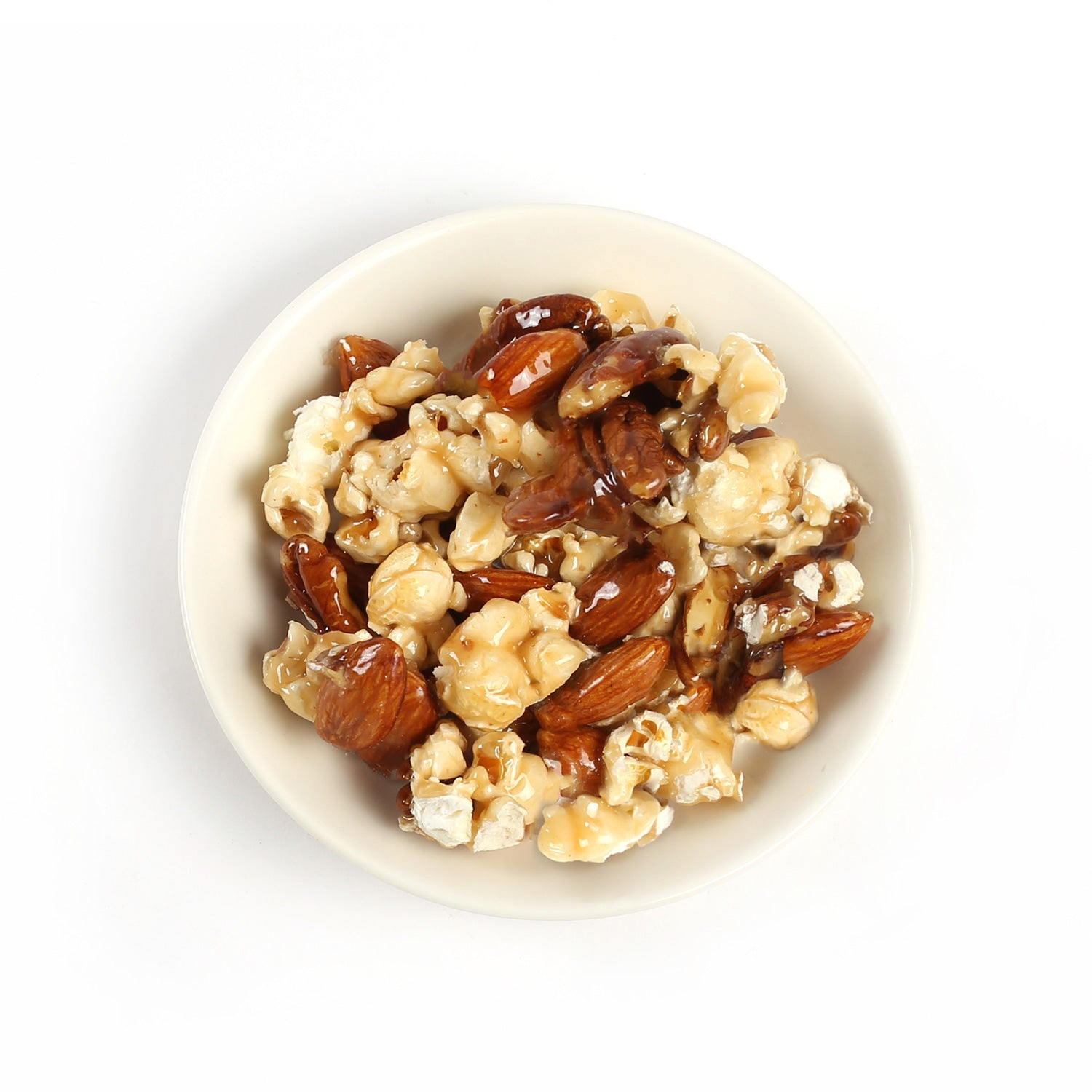 A mix of buttery rich, caramel coated pecans, almonds and fresh popcorn, packaged in a paper bag with a clear window.