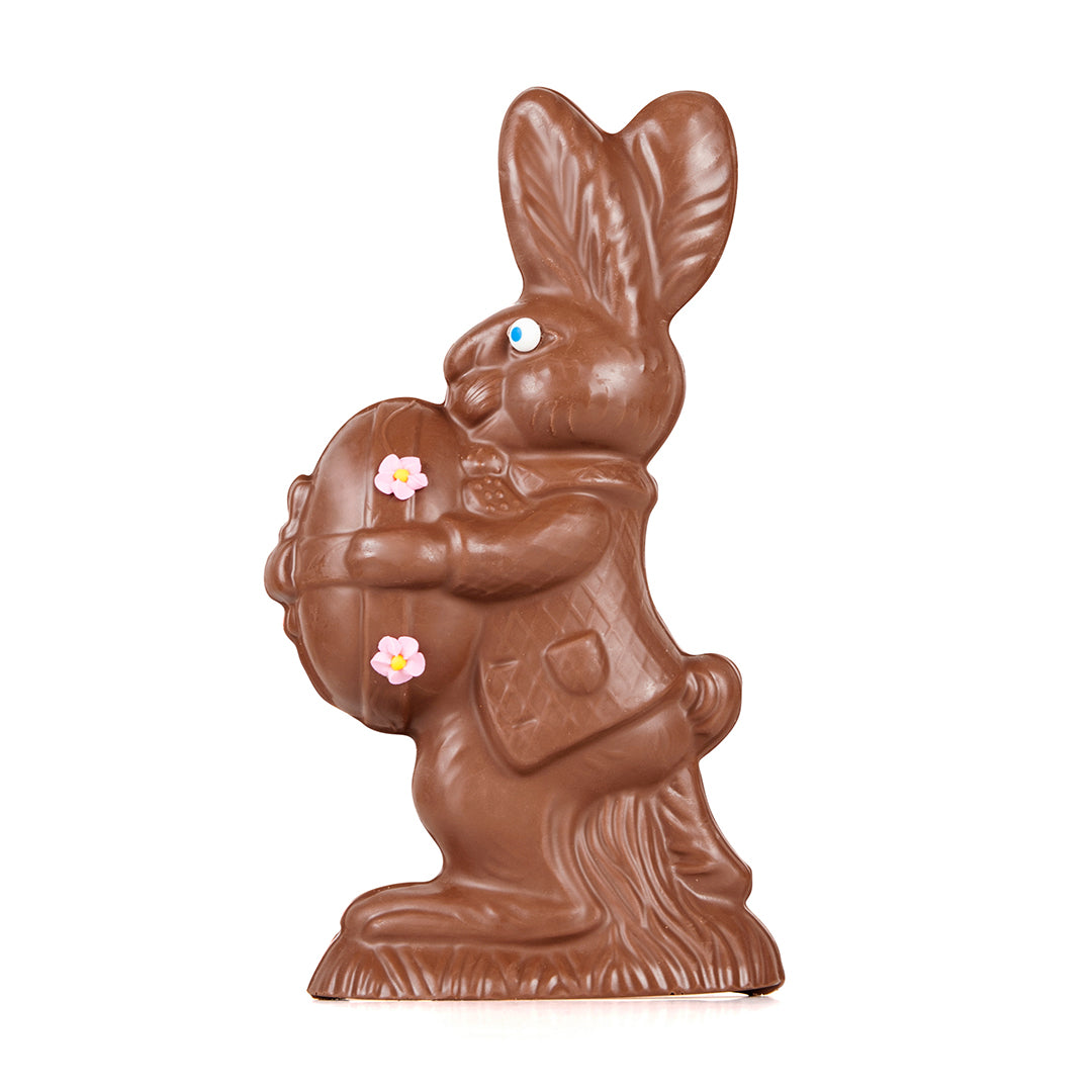 A large milk chocolate rabbit holding a egg.