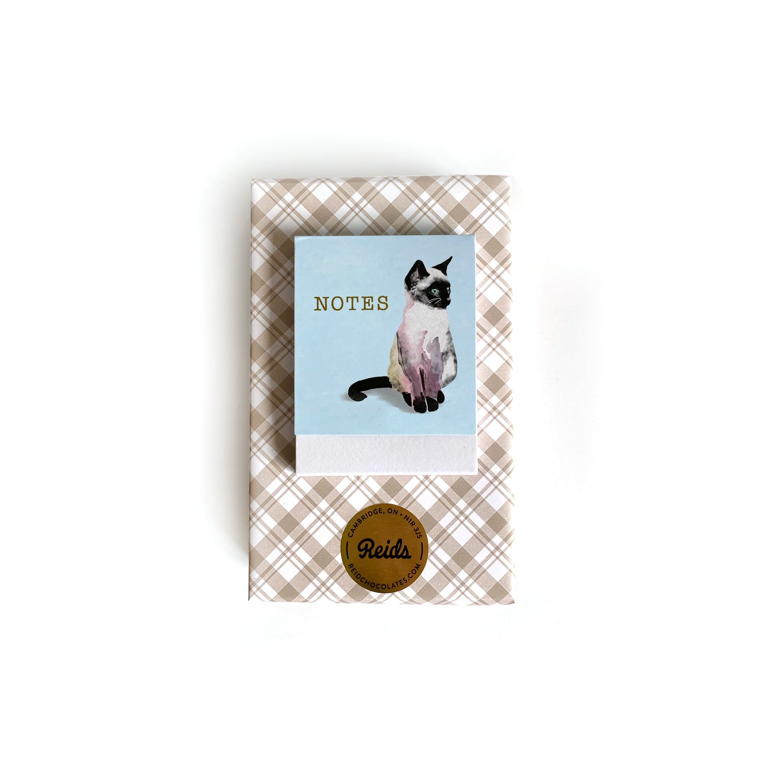 A beige plaid wrapped bow with a siamese cat notebook.
