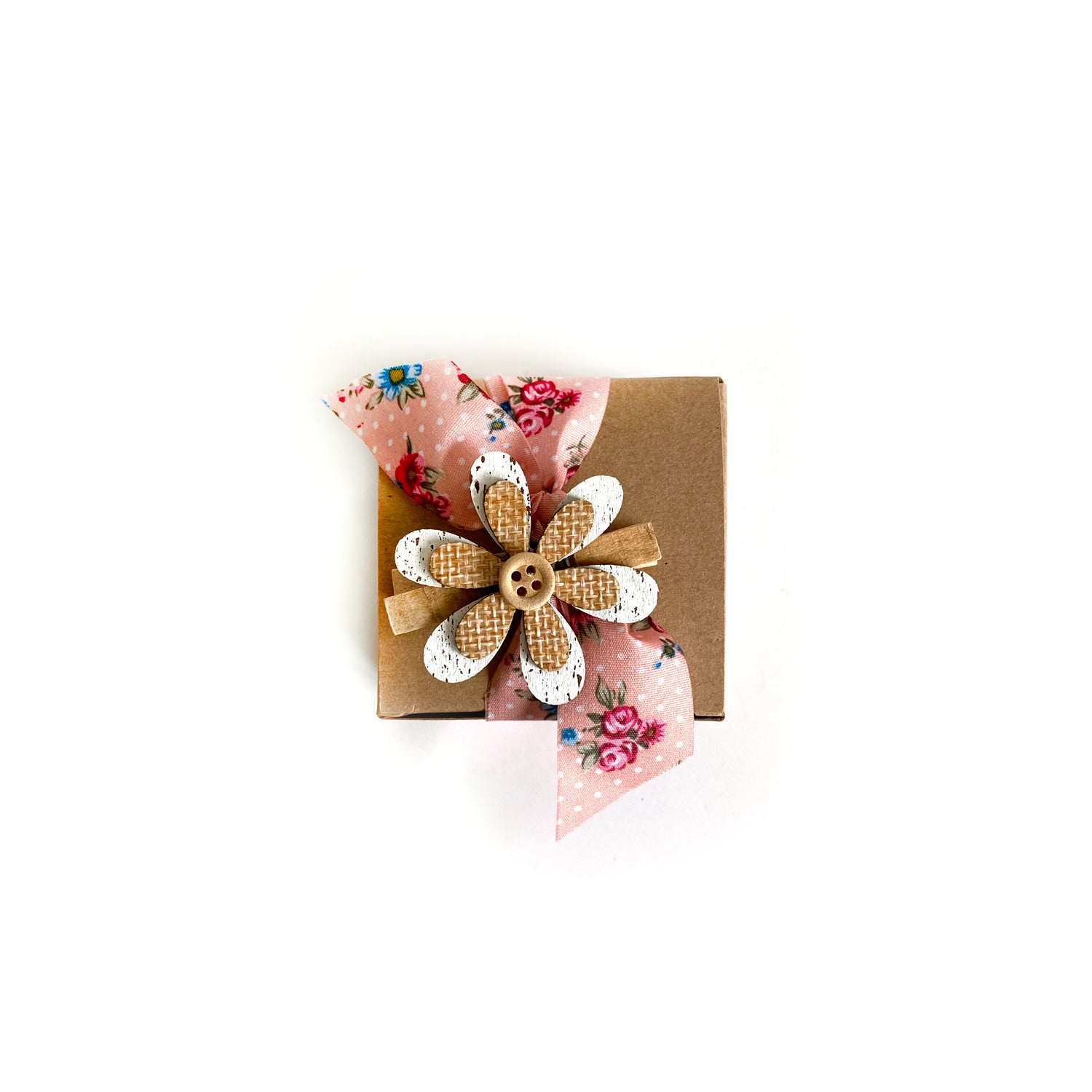 A small kraft box with a pink floral bow and wooden flower.