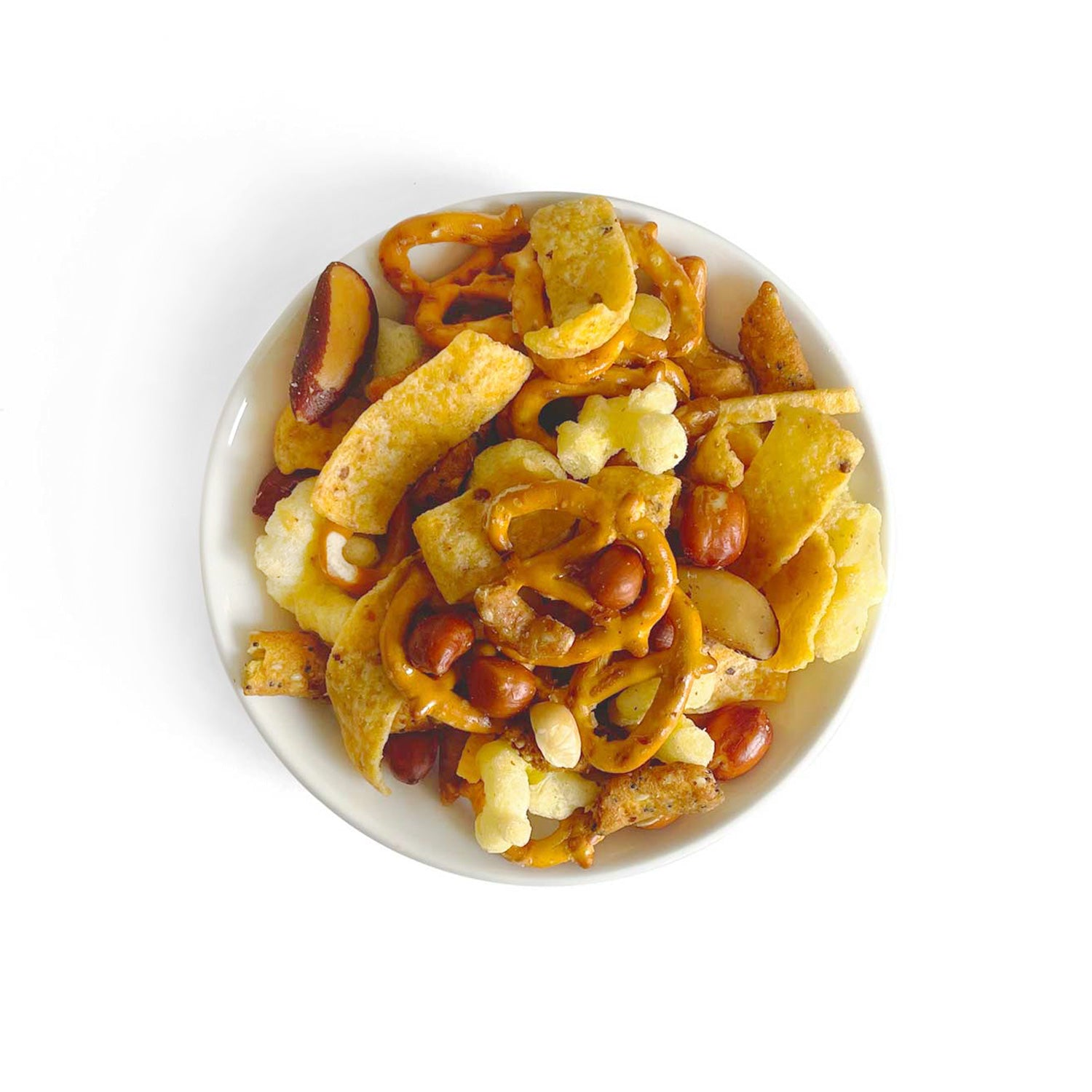 A bowl full of a new twist on a classic snack mix! Contains corn chips and corn puffs, hickory sticks, everything sesame sticks, honey sticks, mini pretzels, salted peanuts, brazils and cashews.