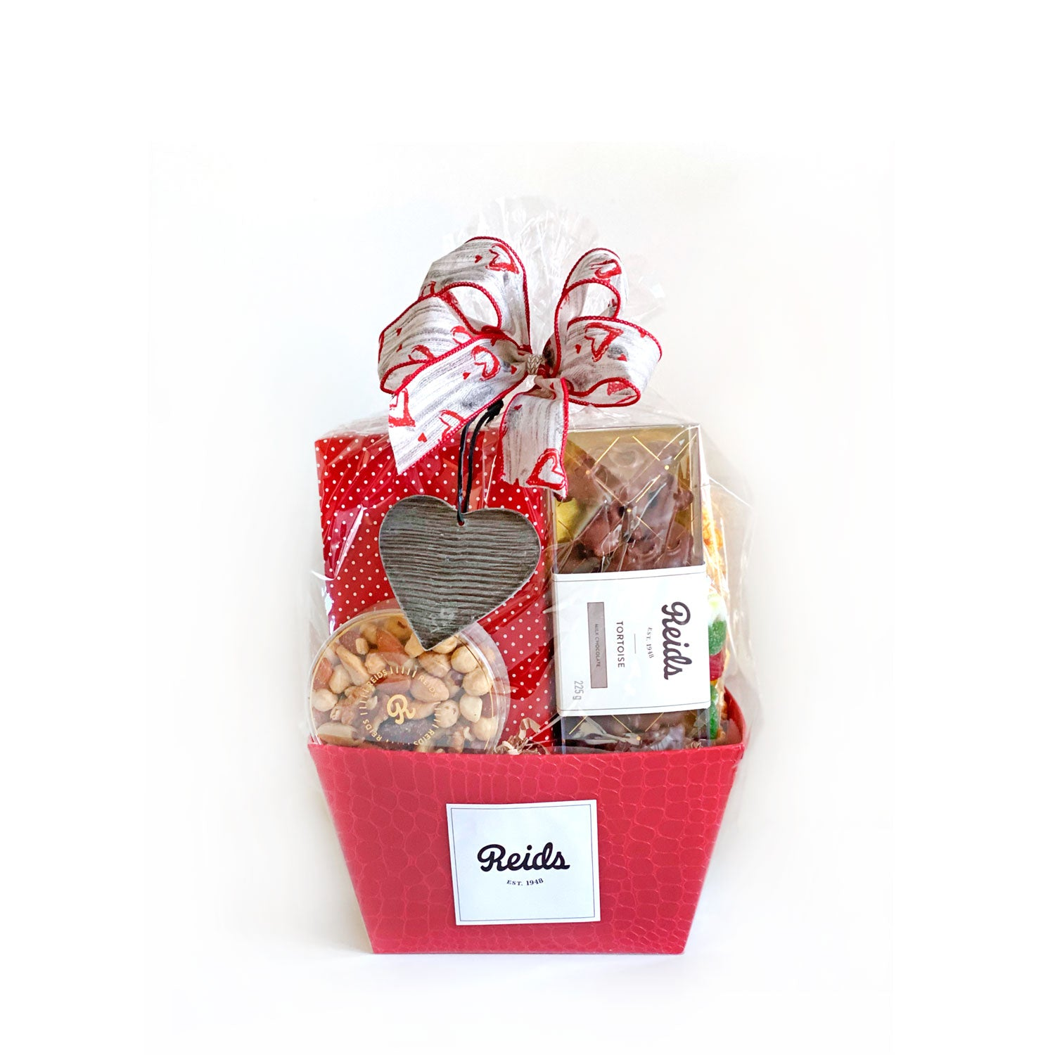A basket filled with 1/2 lb assorted chocolates, 1/2 lb Tortoises, 1/4 lb fancy mixed nuts, 1/2 lb candy bag, 1 bag of Barrie's Kettle Chips, and 1 bag of caramel corn.