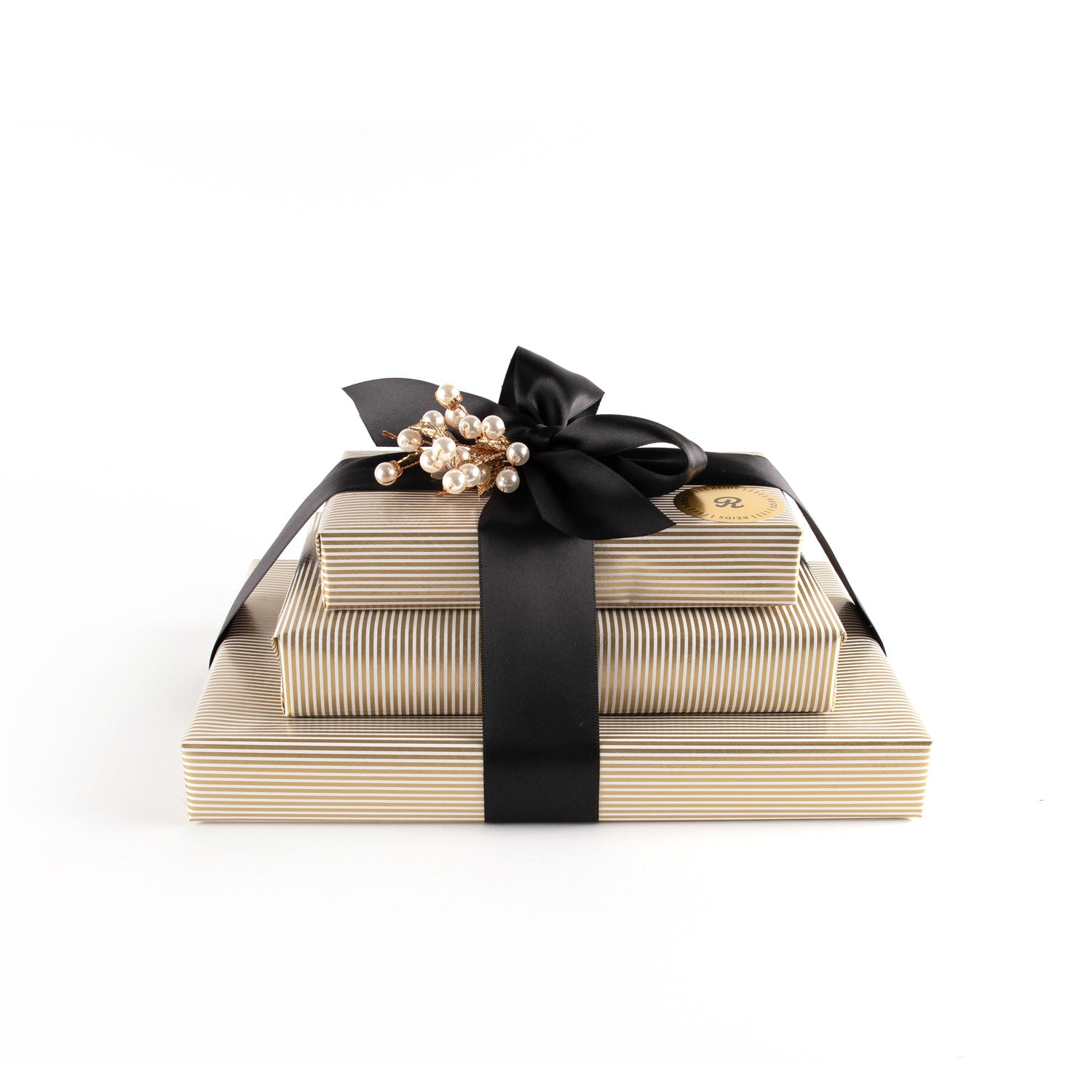 Three stacked Trio Box . Gold, and white pin-stripped wrapping paper. Tied with a black satin ribbon and white decorative piece.