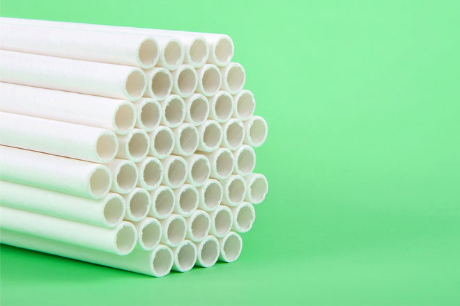 A bundle of white straws is stacked up on a light green background, facing to the right.