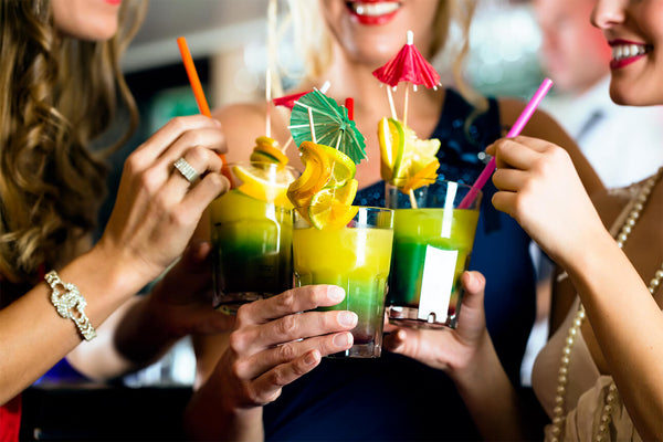 "A group of friends ""cheers"" their drinks and sip out of different colored paper straws."