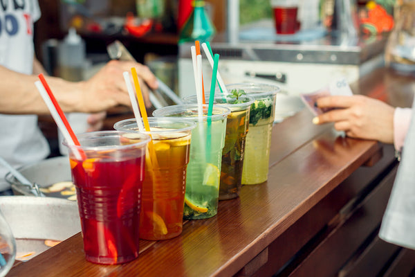 5 cups filled with colorful drinks with colored paper straws sit on a bar while a woman pays the cashier.