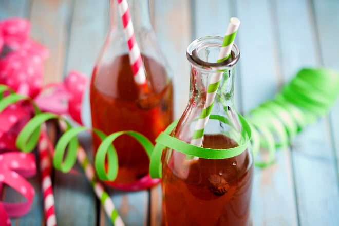 Two glass cola bottles sit on wood planking. They're filled with a fruity beverage and there are two striped paper straws sticking out of them. There are pink an green streamers intertwined with the bottles.
