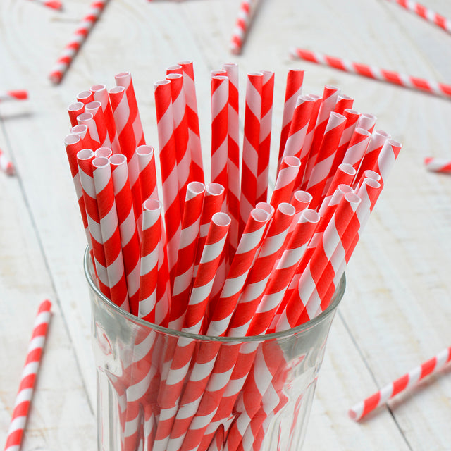 Red and white striped paper straws standing upright in a glass