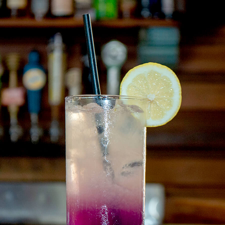 A black paper straw sits in a tall glass full of a purple to yellow gradiented beverage. There is a lemon round garnish on the glass, and the bar is in the background.