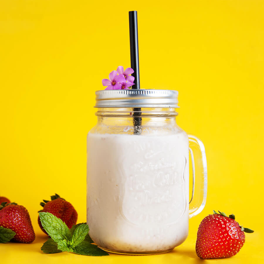 A mason jar full of a strawberry smoothie sits on a yellow background surrounded by strawberries. There is a lid and a giant black paper straw in the jar.