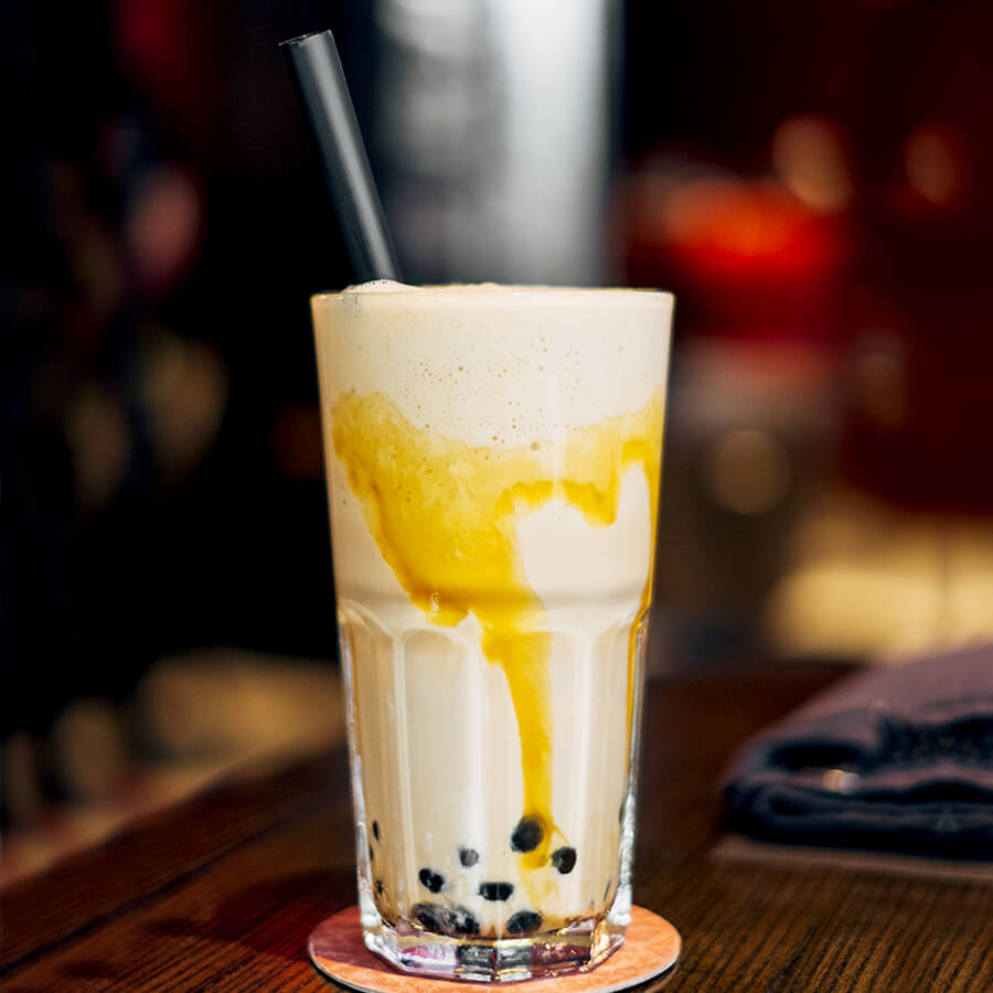 A large glass full of bubble tea sits on a coaster. There's a jumbo black paper straw in the drink.