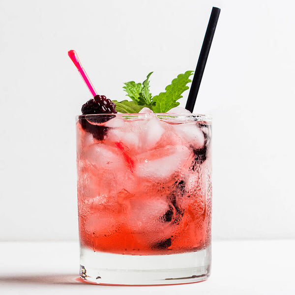A cocktail glass sits on a table, filled to the brim with ice and a red beverage. It is garnished with a skewered berry, mint, and a black paper cocktail straw.