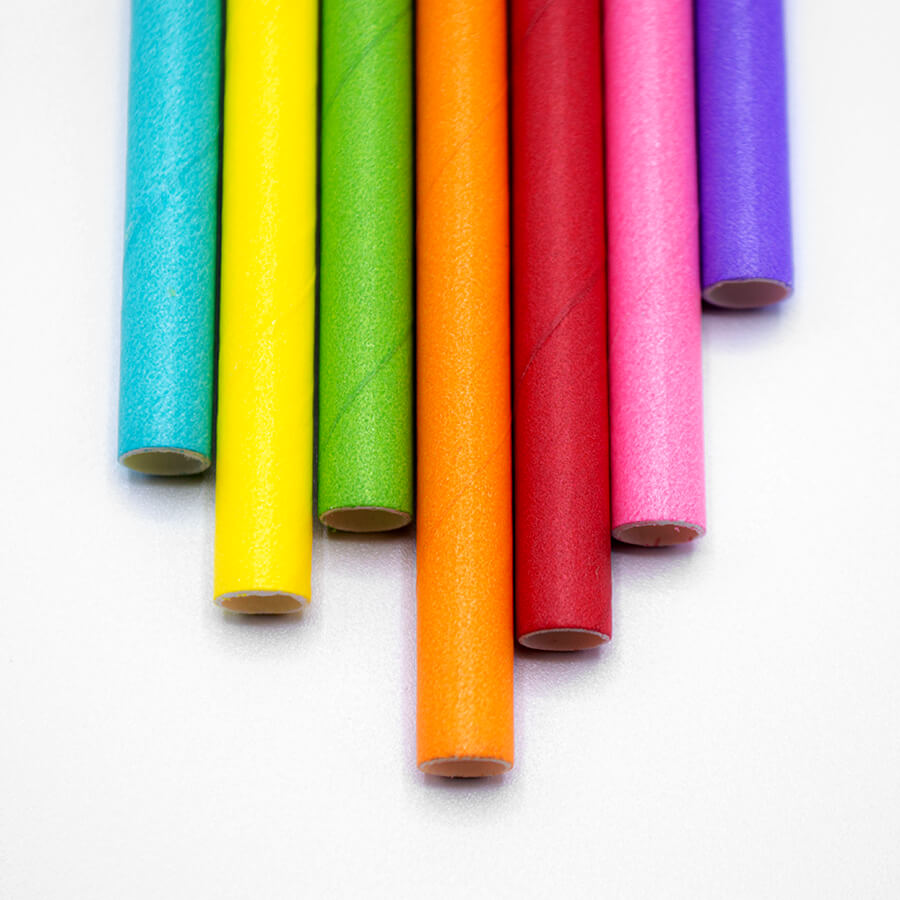 7 paper straws are lined up at varying heights. There is a blue paper straw, a green paper straw, a yellow paper straw, an orange paper straw, a red paper straw, a pink paper straw, and a purple paper straw.