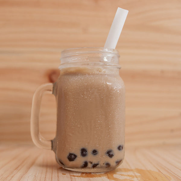 A mason jar full of boba tea sits on a wooden table. There is a large white paper straw in the tea.