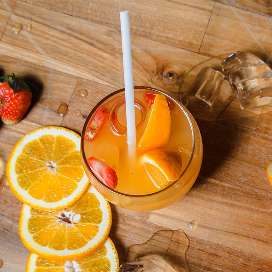 A regular white paper straw sits in a cup of orange juice filled with sliced strawberries and oranges.