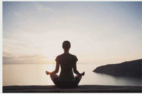 woman meditating at sunrise looking over water