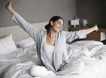 woman stretching on bed in morning happy