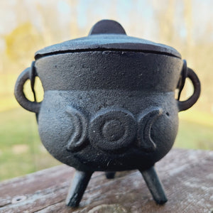 "Cast iron cauldron with lid and handle.  Outer dimensions are 4.5"" wide x 4"" tall with the lid on.  Inside diameter is 2.75"" and 2.25"" deep.  Two half moons with a full moon in the middle is on both sides of the cauldron."