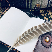 Load image into Gallery viewer, leather bound journal with tigers eye stone laying open with quill and ink