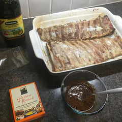 applying the sauce or marinade to the ribs