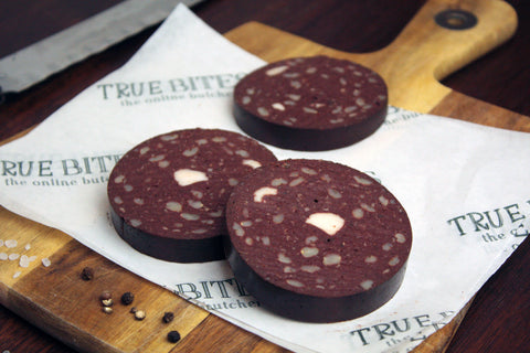 sliced black pudding displayed on true bites branded greaseproof paper