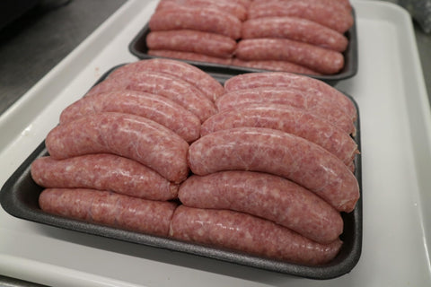black tray filled with thick premium pork sausages
