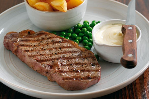 cooked sirloin steak pictured on a white plate with chips, peas and a garlic dip