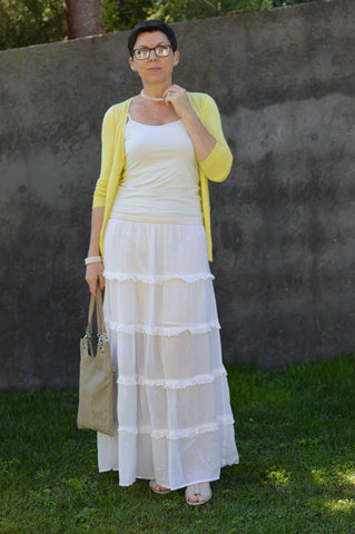 suzy turner wearing a yellow jumper and a skirt with calla wedge sandals
