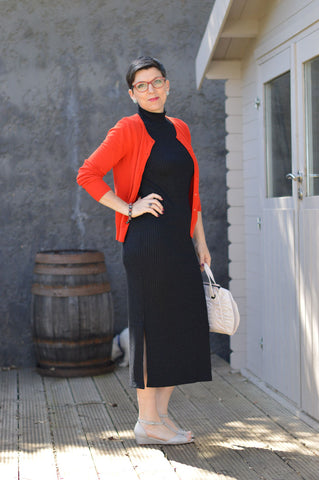 suzy turner wearing wedge sandals for bunions with a black dress and a red jumper