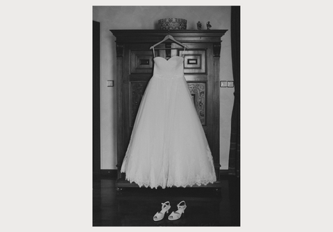 black and white photo of a wedding dress and wedding shoes