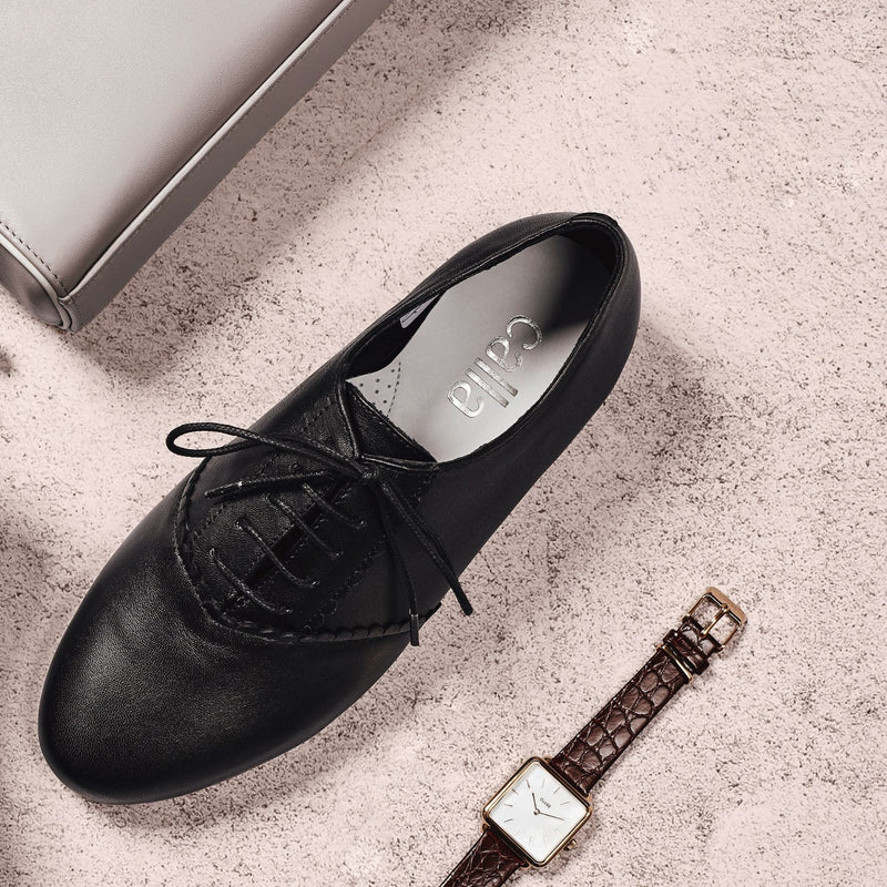 black leather brogue shoes paired with a watch