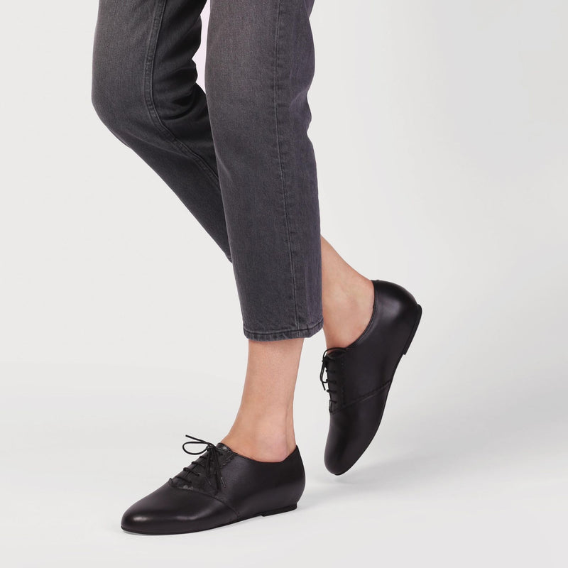 aster black leather brogue shoes worn by a model