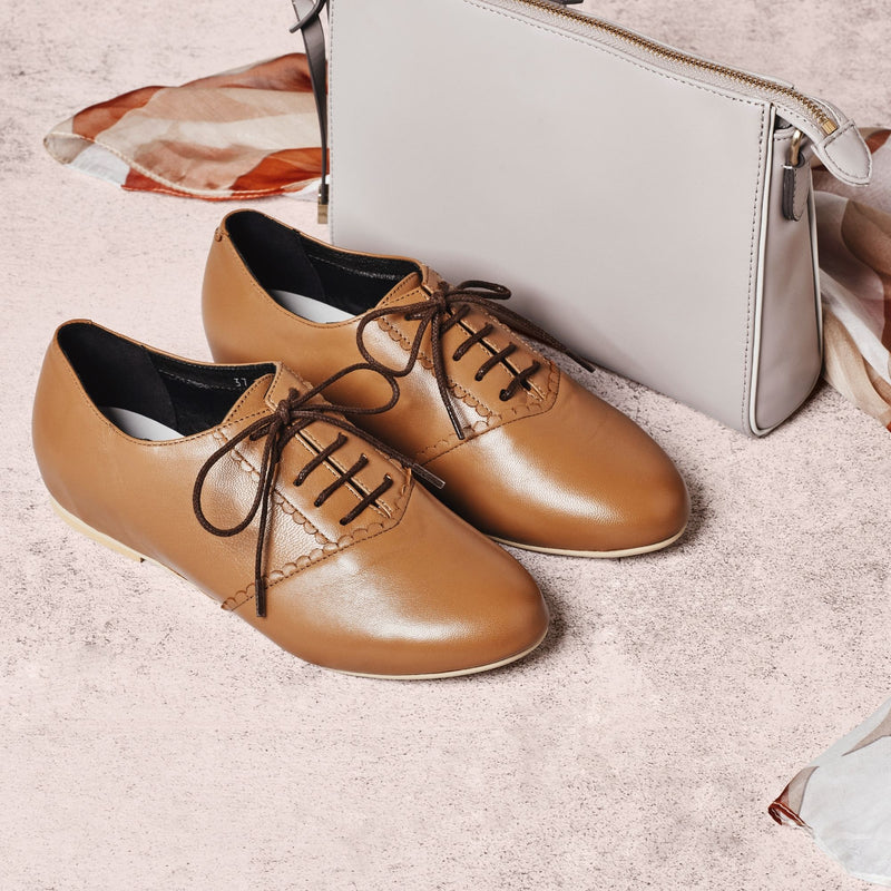 tan leather brogue shoes paired with a handbag