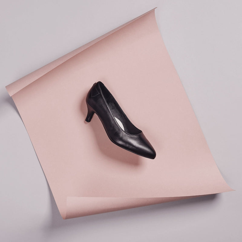 black leather low heel shoe on a pink background
