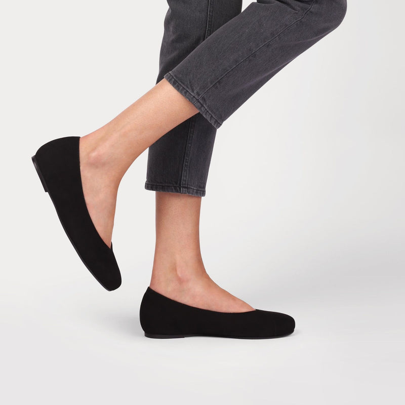 black suede flats worn by a model